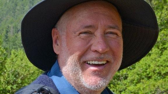 Freundlich lächelnder Mann mit kurzem weißem Bart und einem breitkrempigen Hut vor einer Landschaft.