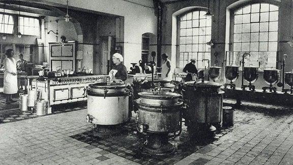 historische Aufnahme / In einer Küche stehen mehrere Frauen an hüfthohen Metallkübeln.