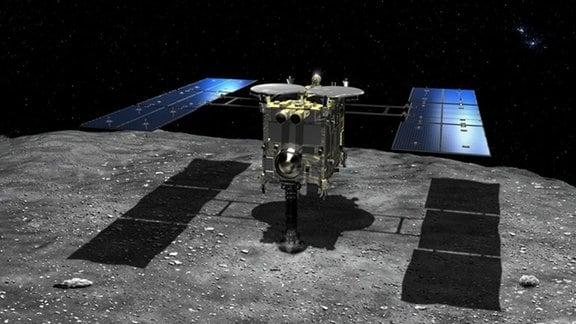 Grafik: Raumsonde mit Mittelteil und zwei Sonnenkollektoren schwebt über der Oberfläche des Asteroiden Ryugu