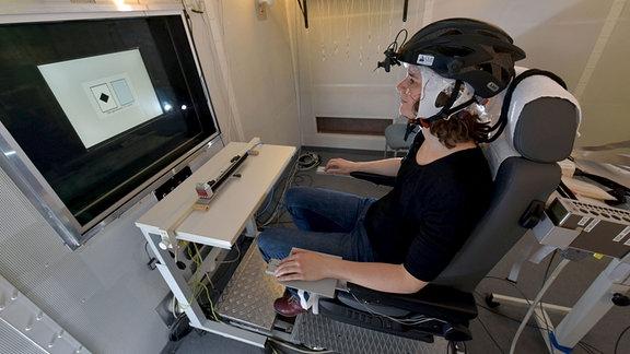 Probandin sitz mit aufgesetzten Helm vor Monitor und löst Aufgaben.
