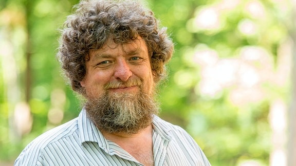 Porträt von Prof. Helmut Hillebrand: Man mit grau-blond-lockigen Haaren, Bart und freundlichem Gesichtsausdruck. Trägt gestreiftes Hemd. Im Hintergrund unscharf Natur und Grün.
