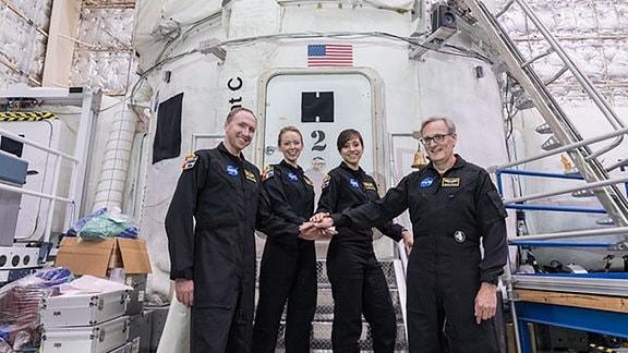 Vier Astronauten stehen vor einer weißen Raumbasis.