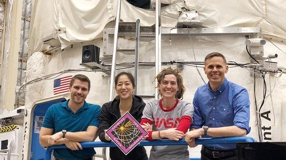 Vier Astronauten stehen vor einer weißen Modul-Raumbasis.