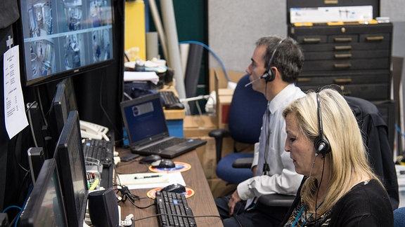 Zwei Menschen sitzen vor Bildschirmen, auf denen die Bilder von Überwachungskameras zu sehen sind.