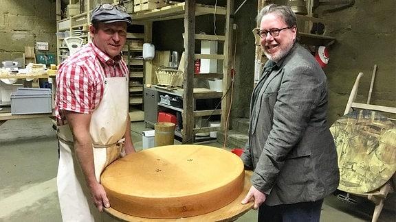Zwei Männer halten einen Käselaib