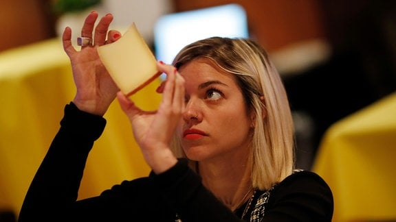 Eine junge Frau betrachtet eine Scheibe Käse