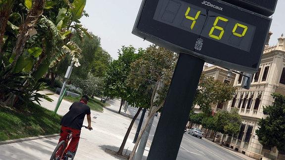 Ein Mann fährt am 12. Juli 2021 in der Stadt Murcia, Spanien, neben einem Thermometer, das 46 Grad anzeigt, Fahrrad.