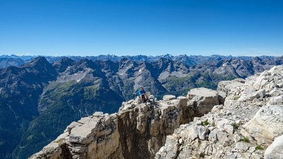 Wanderer sitzt auf Felsen, Aussicht vom Gipfel des Hochvogel