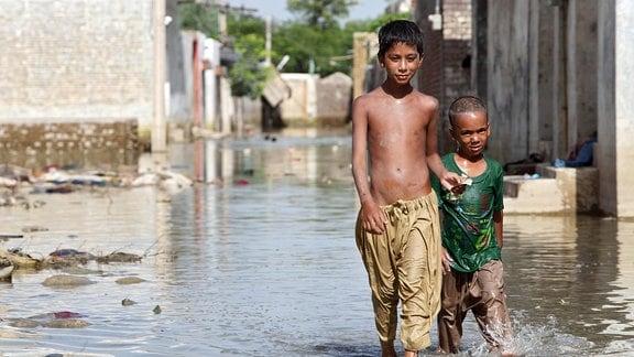 Kinder laufen in Nowshera, Pakistan, durch eine überschwemmte Straße
