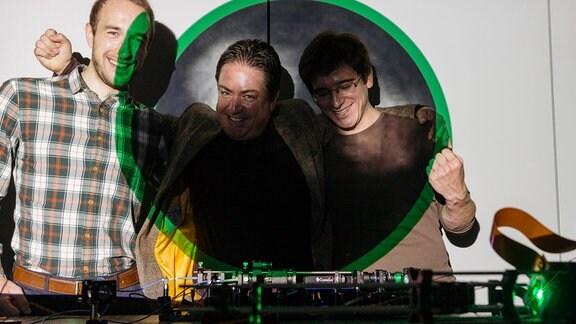 Drei jubelnde Männer vor einem technischen Gerät stehen vor einer Wand, auf die auch ein Bild des holografischen Endoskops projiziert wird.