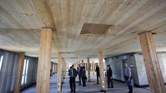 Besucher des Hochhauses schauen sich die Holzstruktur im Inneren des Hauses an.