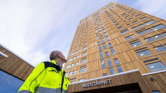 Ein Mann in neongelber Schutzkleidung, der nach oben schaut - auf ein Hochhaus aus Holz.
