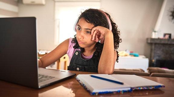 Ein Mädchen sitzt vor einem Laptop
