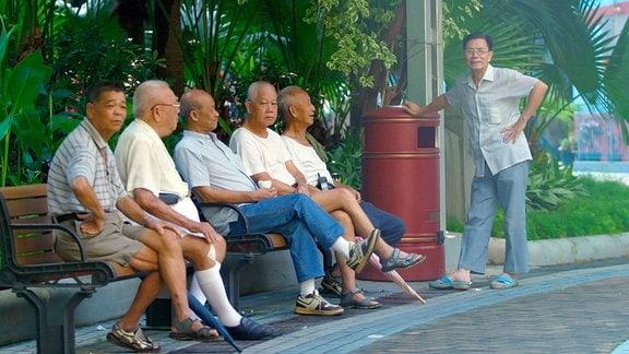 Eine Gruppe älterer Männer enspannt sich auf einer Parkbank in Hong Kong.