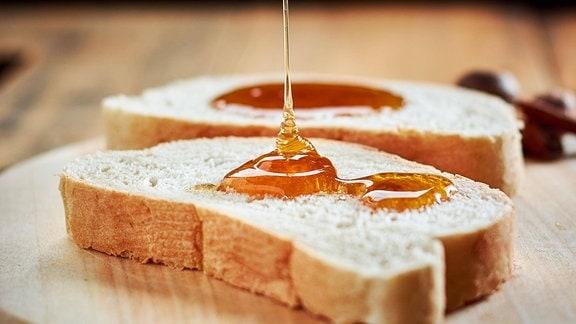 Honig wird auf Brotscheiben getropft.
