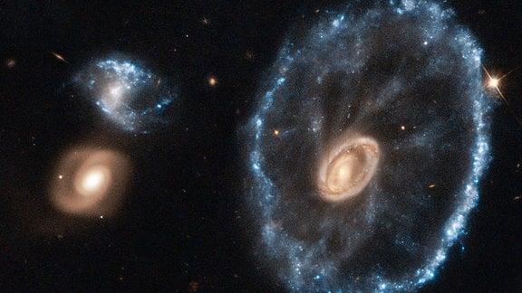 Hubblefoto ein Galaxie, die wie ein Wagenrad aussieht. Die besondere Form ist Ergebnis einer galaktischen Kollission: Eine kleinere Galaxie hat die Größere durchstoßen.