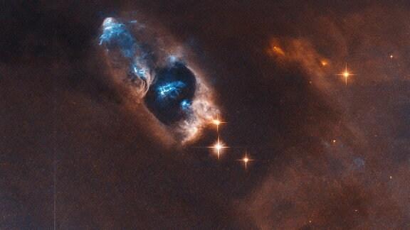 Ein junger Stern hat fünf Objekte hervorgebracht, die hier am oberen Bildrand blau erscheinen. Diese fünf Herbig-Haro-Objekte entfernen sich mit hoher Geschwingidkeit von ihrem Ursprungsstern.