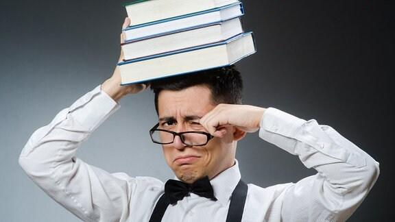 Ein Mann mit vier Büchern auf dem Kopf