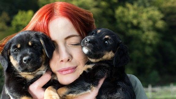 Junge Frau hält zwei Hunde in ihren Händen.