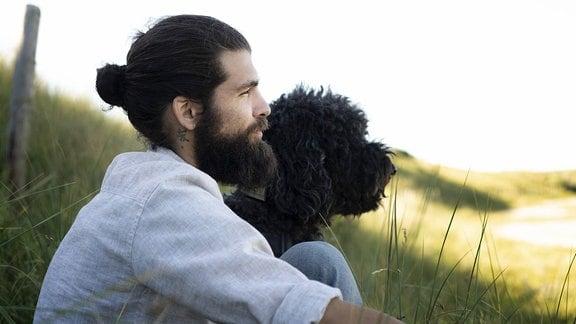 Junger Mann, der mit seinem Hund in den Dünen sitzt