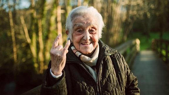 Ältere Frau mit Hörner-Geste mit der rechten Hand lacht in die Kamera, Außenaufnahme, im Hintergrund Natur