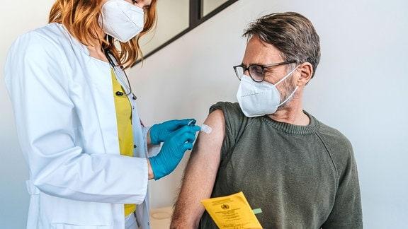 Mann bekommt Pflaster auf den Arm geklebt.
