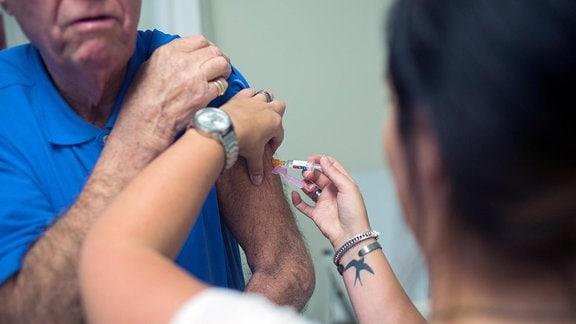 Älterer Mann (Gesicht nur angeschnitten) mit hochgekrempelten Oberteil erhält von einer Frau (im Vordergrund unscharf) eine Impfung. Blick über die Schulter der Frau.