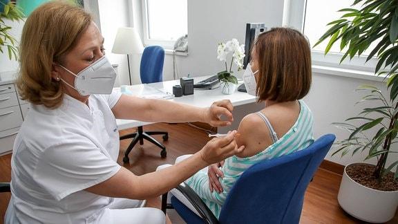 Eine Ärztin impft Patientin gegen Corona.