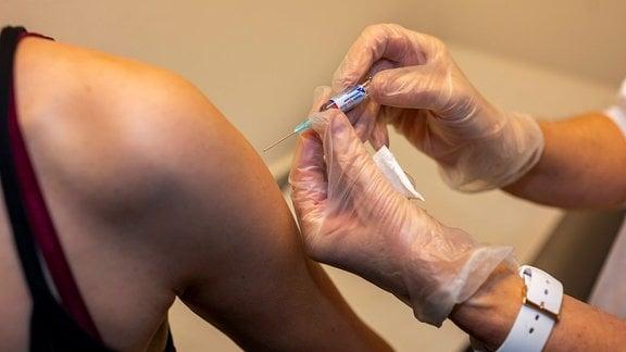 Eine Ärztin gibt einer Frau eine Spritze als Grippeschutzimpfung.