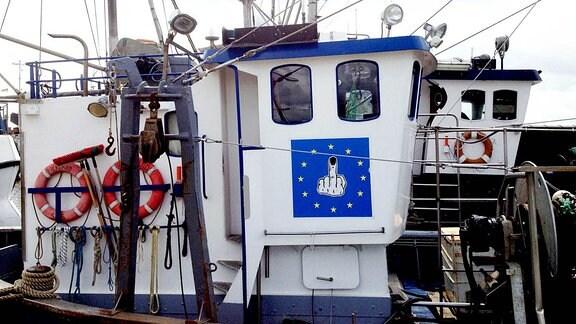 Ein Fischerboot mit einer Anti-EU-Flagge: Zu sehen ist eine blaue Fahne mit dem Kreis aus Sternen. In der Mitte ist eine Hand zu sehen mit einem hoch gestreckten Mittelfinger. Der Mittelfinger ist ein Fisch.