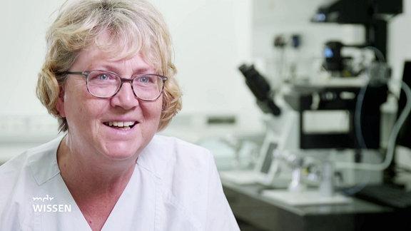 Frau mit Brille im weißen Ärztekittel lächelt