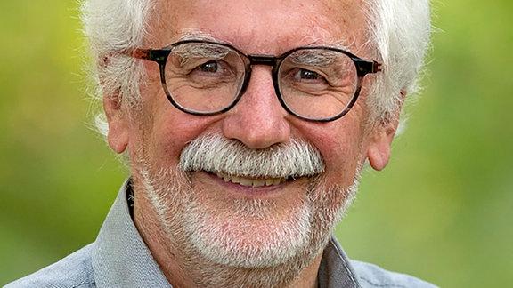 Lächelnder Mann mit grauem Bart und grauen Haaren, einer dunklen, fast runden Brille und einem graublauen Hemd, der freundlich in die Kamera blickt.