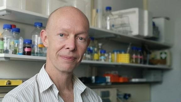 Porträtaufnahme eines Mannes mit Glatze, der in einem Labor steht.