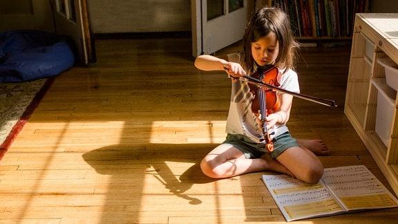 Mädchen sitzt auf dem Boden und spielt Geige.