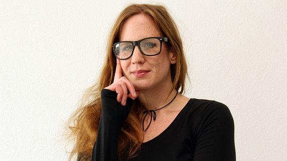 Eine junge Frau mit langen Haaren trägt eine schwarze Hornbrille und fasst sich mit Zeigefinger und Daumen ans Kinn.