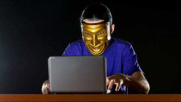 Ein Mann sitzt mit einer Maske vor einem Laptop.