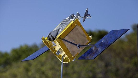 Das Model eines ''OneWeb''-Satelliten (goldener Kasten mit zwei Solarzellenflügel) an einer Eisenstange.