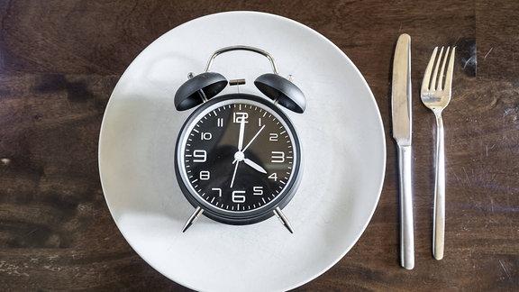 Auf einem Teller liegt ein Wecker