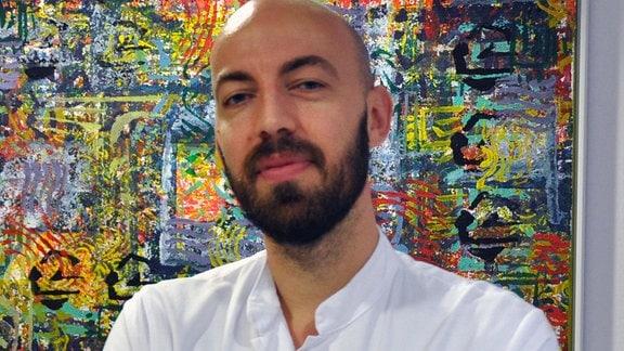 Ivan Tancevski vor einem Gemälde.