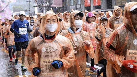 Läufer tragen bei einem Marathon in Kumamoto Atemschutzmasken