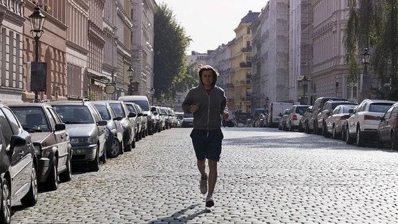 Junger Mann joggt auf Kopfsteinpflaster mittig Richtung Kamera, links und rechts Gründerzeithäuser und parkende Autos