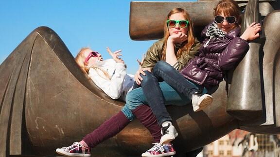 Drei junge Mädchen mit Sonnenbrillen sitzen auf einer Bronzeskulptur