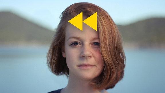 Junge Frau oder Mädchen, deren rechte Gesichtshälfte mit einer Software gealtert dargestellt wird. Gelbes Rückspul-Symbol auf Stirnhöhe. Frau mit rotblonden kinnlangen Haaren blickt in die Kamera, Hintergrundlandschaft unscharf. Neutraler Blick.