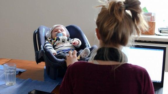Junge Frau mit Kleinkind arbeitet im Homeoffice