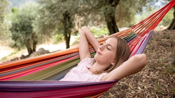Eine junge Frau liegt mit geschlossenen Augen in einer Hängematte
