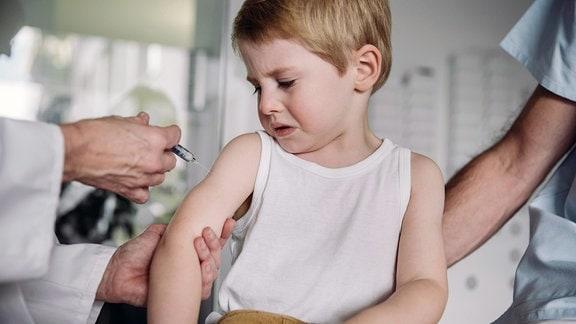 Ein Arzt impft einen Jungen, dieser schaut mit verzerrtem Gesicht darauf.