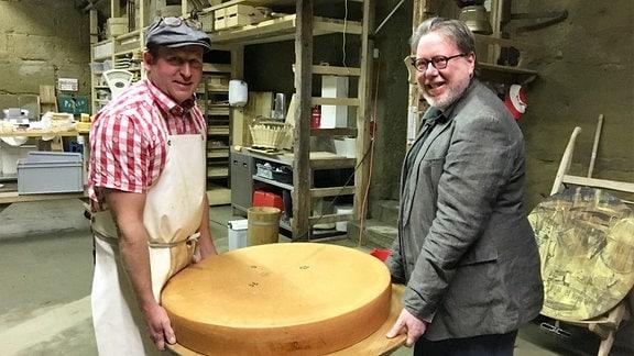 Zwei Männer (links: Beat Wampfler, rechts Michael Harenberg) halten eine eine Holzplatte mit einem Käse, der rund ist une etwa ein Meter Durchmesser hat.