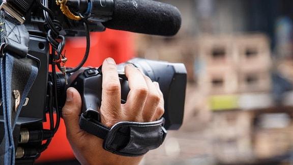 Hand an einem TV - Kameraobjektiv