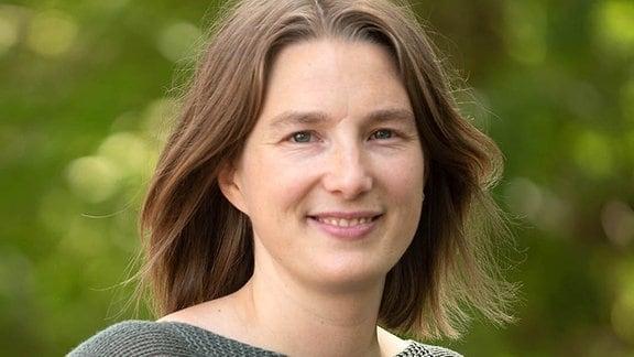 Karolin Dörner: Weiße junge Frau mit mittellangen, offenen Haaren mit Mittelscheitel. Hintergrund tiefenunscharf mit viel grün.