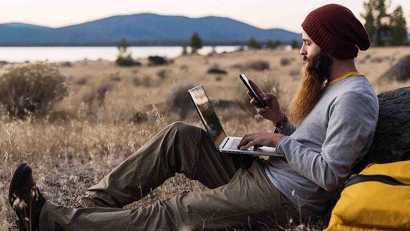 Ein junger Mann mit langem Bart und Mütze benutzt ein Smartphone und einen Laptop in der Natur.